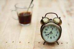 Despertador análogo na tabela de madeira com fundo do jardim do verde do borrão, 8 am , espaço da cópia fotografia de stock royalty free