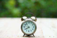 Despertador análogo na tabela de madeira com fundo do jardim do verde do borrão, 8 am , espaço da cópia imagens de stock