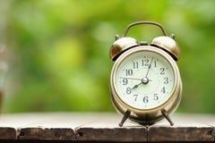Despertador análogo na tabela de madeira com fundo do jardim do verde do borrão, 8 am , espaço da cópia fotos de stock