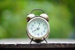 Despertador análogo na tabela de madeira com fundo do jardim do verde do borrão, 8 am , espaço da cópia imagem de stock royalty free