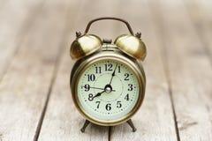 Despertador análogo na tabela de madeira com fundo do jardim do verde do borrão, 8 am , espaço da cópia imagens de stock royalty free