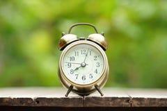 Despertador análogo na tabela de madeira com fundo do jardim do verde do borrão, 8 am , espaço da cópia fotos de stock royalty free