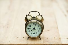 Despertador análogo na tabela de madeira com fundo do jardim do verde do borrão, 8 am , espaço da cópia imagem de stock