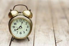 Despertador análogo na tabela de madeira com fundo do jardim do verde do borrão, 8 am , espaço da cópia fotografia de stock