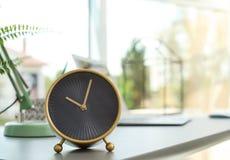 Despertador análogo na tabela no escritório imagens de stock royalty free