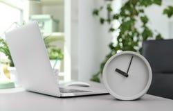 Despertador análogo na tabela no escritório fotos de stock