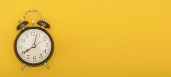 Despertador análogo no fundo amarelo da cor, tema do sincronismo foto de stock