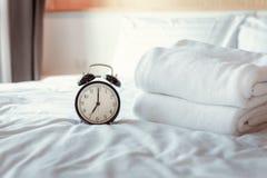 Despertador análogo no quarto na casa moderna, temporizador retro em 7 00 a M na cama branca da tampa imagens de stock royalty free