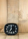 Despertador análogo preto no assoalho de madeira imagem de stock royalty free