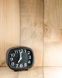 Despertador análogo preto no assoalho de madeira fotografia de stock