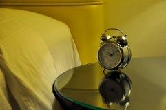 Despertador ao lado de uma cama fotografia de stock