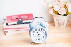 Despertador azul claro en la tabla de madera con los libros y los vidrios Fotos de archivo