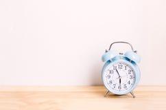 Despertador azul claro en la tabla de madera y el fondo blanco de la pared Imagen de archivo