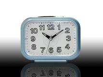 Despertador azul com sombra no fundo preto do inclinação Fotos de Stock Royalty Free