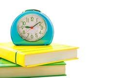 Despertador azul nos livros isolados no fundo branco Foto de Stock