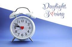 Despertador blanco del estilo retro del vintage en fondo azul y blanco con el texto de la muestra del ahorro de luz del día Foto de archivo