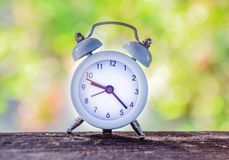 Despertador blanco, en fondo de la naturaleza del bokeh Blurred imagen de archivo