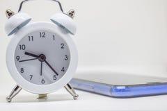Despertador blanco y teléfono azul en el fondo blanco imágenes de archivo libres de regalías