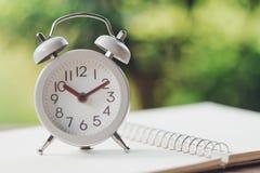 Despertador branco do vintage sobre em um caderno É hora de descansar usando-se como o conceito de relaxamento do tempo do fundo  fotografia de stock royalty free