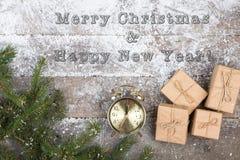 Despertador, cajas de regalo y rama de árbol de abeto en un nevado, texto 'Feliz Navidad y Feliz Año Nuevo ' imagen de archivo