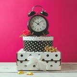 Despertador com as caixas dos às bolinhas sobre o fundo moderno cor-de-rosa Objetos femininos do encanto Foto de Stock