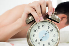 Despertador com o homem que acorda na cama no fundo Imagem de Stock Royalty Free