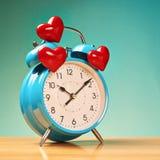 Despertador com três corações sobre Foto de Stock