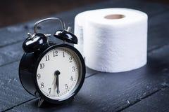 Despertador con el papel higiénico en una tabla Foto de archivo