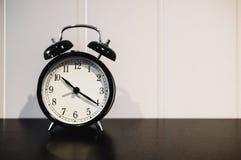 Despertador con el reloj del ` de 10 O y el minué veinte, en la tabla de madera negra con la pared blanca Imagen de archivo