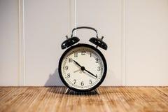 Despertador con el reloj del ` de 10 O y el minué veinte, en la tabla de madera y la pared blanca Foto de archivo libre de regalías