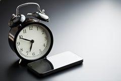 Despertador con el teléfono móvil Imagen de archivo