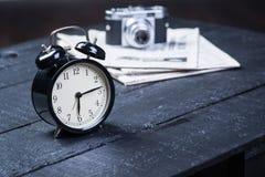 Despertador con la cámara y periódico en la tabla Fotografía de archivo libre de regalías
