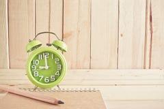 Despertador, cuaderno y lápiz en la tabla de madera Imagenes de archivo