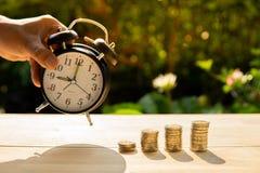 Despertador da captura do homem e a pilha da barra das moedas do dinheiro no fundo de madeira da tabela e do por do sol nas econo imagens de stock