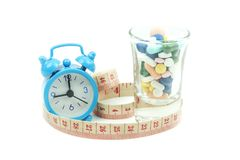 Despertador da medicamentação e uma fita métrica Foto de Stock Royalty Free