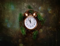 Despertador de cobre del vintage cinco minutos a las ramas de árbol de medianoche de abeto de la guirnalda de la Navidad de la cu Foto de archivo libre de regalías
