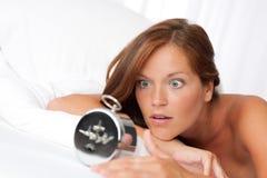 Despertador de observação da mulher Fotografia de Stock
