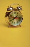 Despertador de oro en un fondo amarillo Fotos de archivo