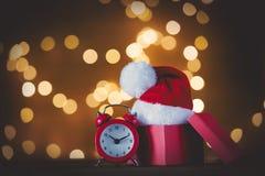 Despertador del vintage con el sombrero de Santa Claus foto de archivo