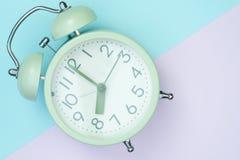 Despertador del vintage en la opinión superior dulce del papel coloreado del pastel, trasera imagen de archivo libre de regalías