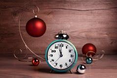 Despertador del vintage que muestra cinco a doce con la chuchería de la Navidad Foto de archivo