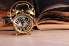 Despertador del vintage que muestra tiempo a través de la lupa Foto de archivo libre de regalías