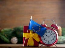 Despertador del vintage y caja de regalo rojos con la bandera de unión de Europa Imagen de archivo