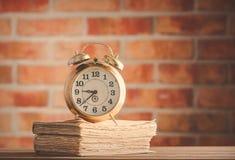 Despertador del vintage y libros viejos en la tabla de madera Fotografía de archivo libre de regalías