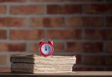 Despertador del vintage y libros viejos en la tabla de madera Foto de archivo libre de regalías