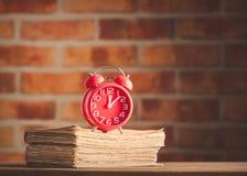 Despertador del vintage y libros viejos en la tabla de madera Imagen de archivo