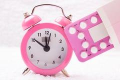 Despertador e comprimidos contraceptivos Fotografia de Stock