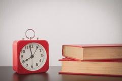Despertador e livro vermelhos na tabela com fundo branco da parede Imagem de Stock Royalty Free