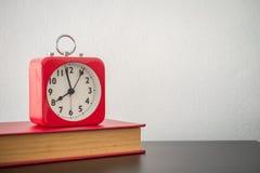 Despertador e livro vermelhos na tabela com fundo branco da parede Fotografia de Stock