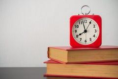 Despertador e livro vermelhos na tabela com fundo branco da parede Fotografia de Stock Royalty Free